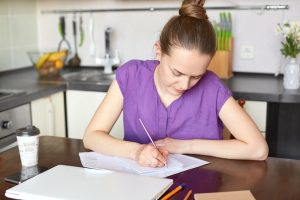 Young woman studying at her kitchen table.