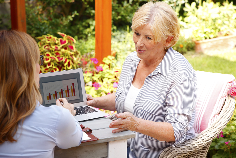 Younger woman advising an older woman on finances in the garden